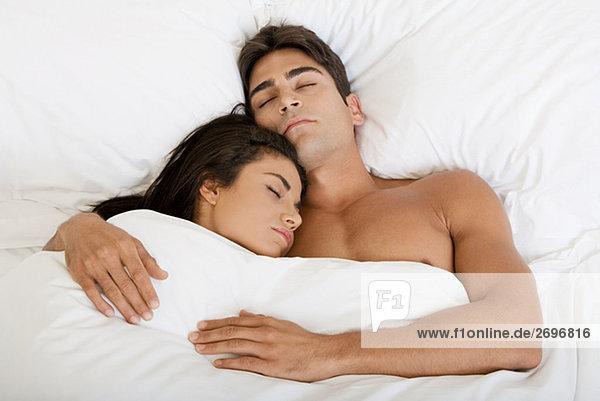 Erhöhte Ansicht eines jungen Paares auf einem Bett schlafen