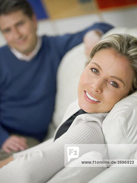 Portrait einer Mitte erwachsen frau sitzt auf einer Couch und lächelnd und ein älterer Mann sitzt im Hintergrund