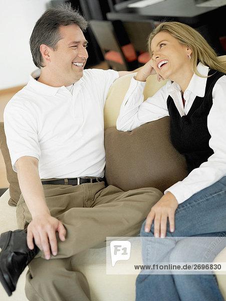 Mitte erwachsen frau und ein älterer Mann auf einer Couch sitzen und Blick auf einander