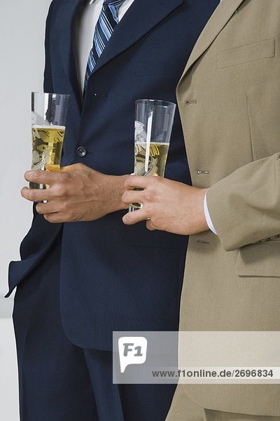 Mid section view of two businessmen holding glasses of beer in a party
