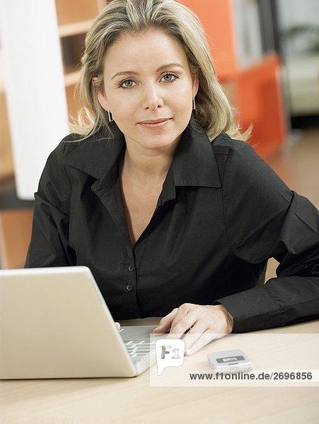 Portrait einer Mitte erwachsen frau an einem laptop