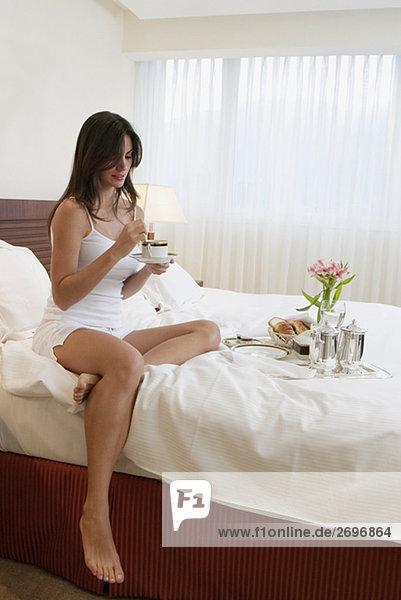 Junge Frau sitzen auf dem Bett mit eine Tasse Tee