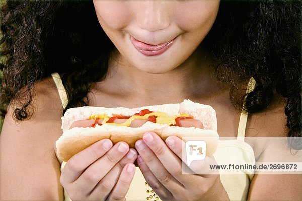 Close-up of a girl holding a hot dog and sticking her tongue out
