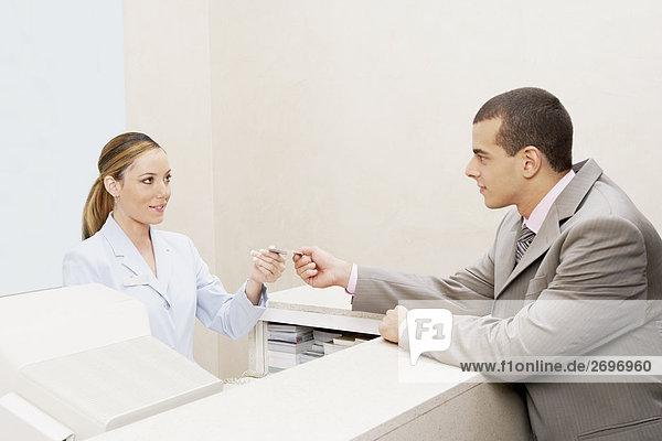 Kunden geben eine Kreditkarte zu einem weiblichen Empfangsdame
