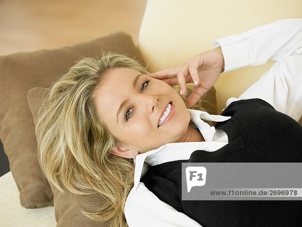 Erhöhte Ansicht einer Mitte erwachsen frau liegend auf einer Couch und lächelnd