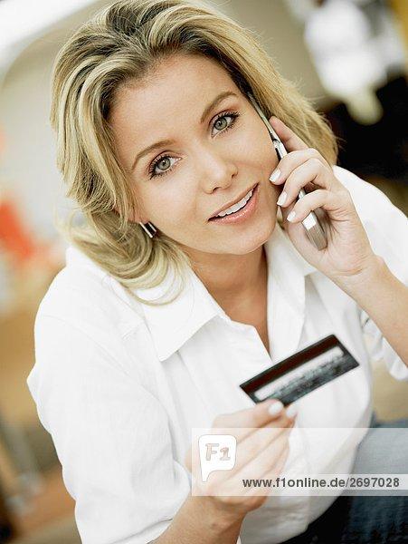 Portrait einer Mitte erwachsen frau Gespräch auf einem Mobiltelefon und halten eine Kreditkarte