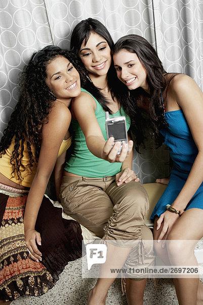 Teenagerin und zwei junge Frauen  die ein Foto von sich selbst