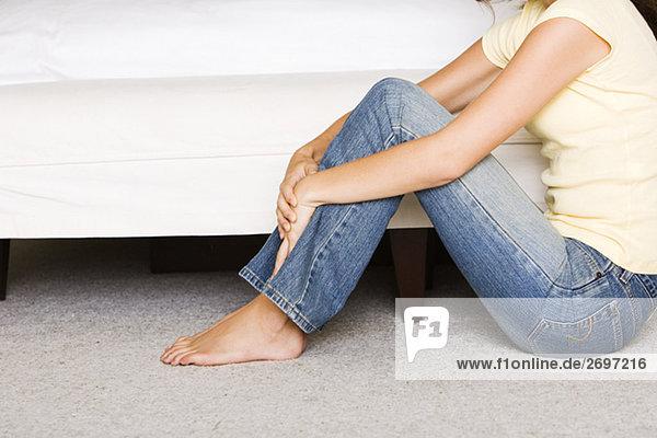 Niedrige Schnittansicht einer jungen Frau sitzen auf dem Boden