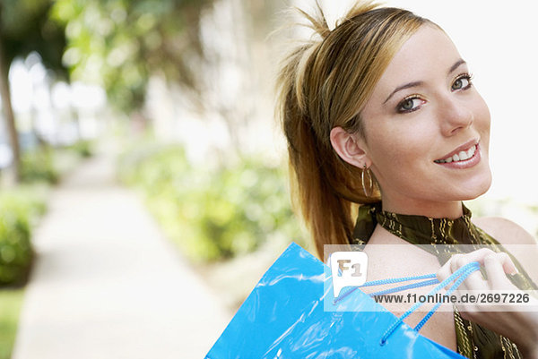 Portrait of a junge Frau hält einer Einkaufstasche