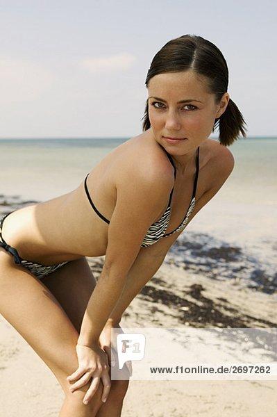 Portrait einer jungen Frau Biegung nach vorn am Strand
