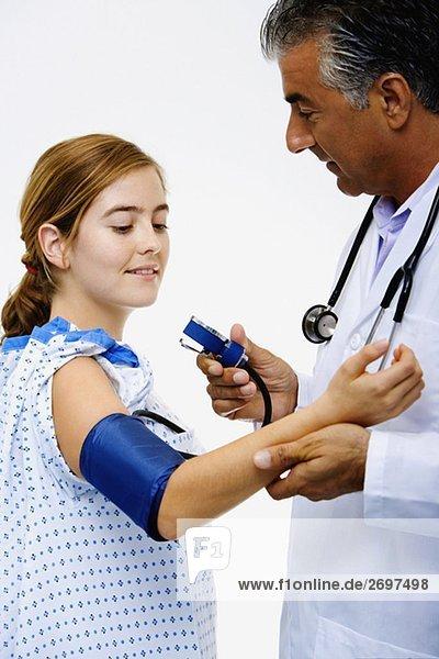 Seitenansicht einen männlichen Arzt messen Blutdruck einer jungen Frau