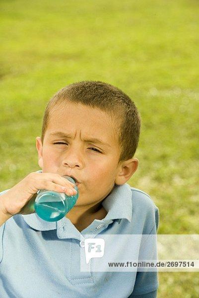 Bildnis eines Knaben aus einer Flasche Getränk trinken