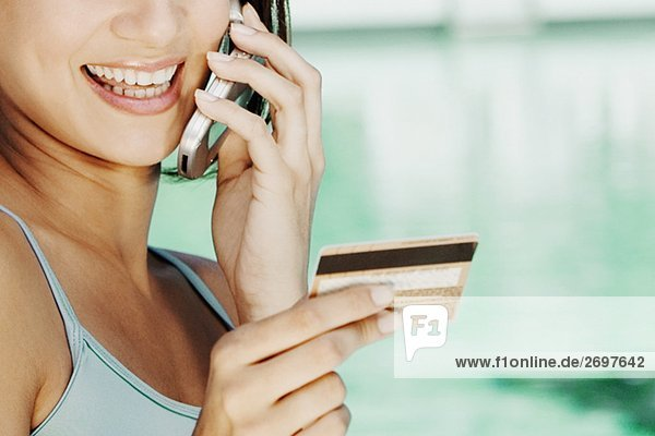 Nahaufnahme of a junge Frau hält eine Kreditkarte und sprechen auf einem Mobiltelefon