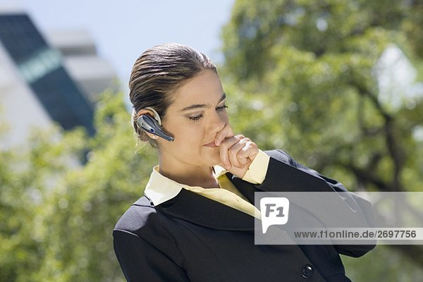 Businesswoman wearing a bluetooth device with her hands covering her mouth