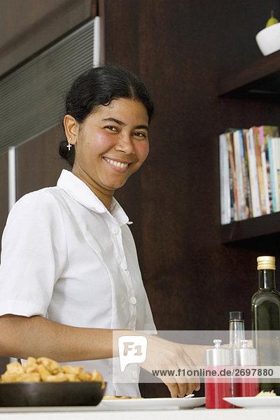 Porträt von Dienstmädchen Essen in der Küche zubereiten und lächelnd