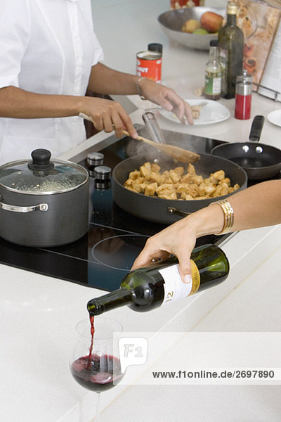 Close-up of a woman's hand pouring red wine into a wine glass with a maid preparing food in the background