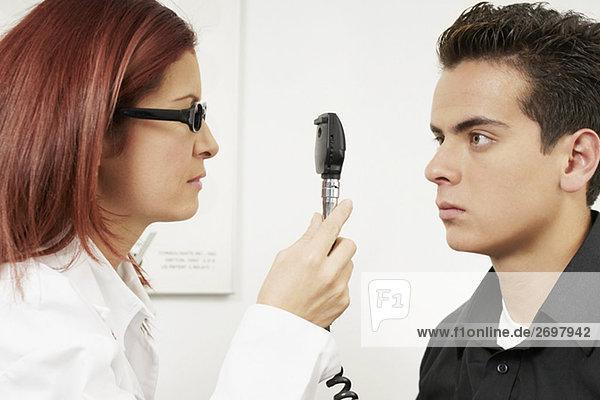 Nahaufnahme von einem weiblichen Optometrist untersuchen Augen eines jungen Mannes
