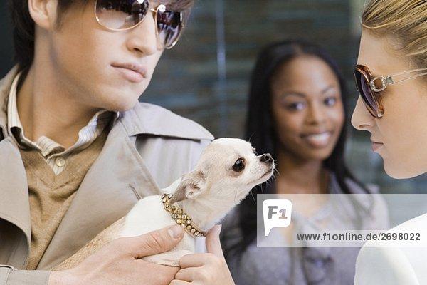 Nahaufnahme eines jungen Mannes halten einen Welpen und eine junge Frau auf der Suche nach ihm