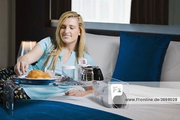 Junge Frau einem Frühstück auf dem Bett