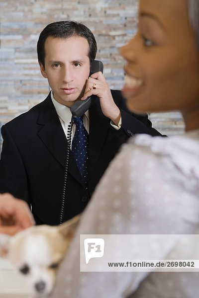 Älterer Mann sprechen auf das Telefon und eine junge Frau hält ein Welpe