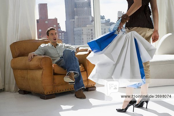Niedrige Schnittansicht einer jungen Frau tragen Tragetaschen mit einem jungen Mann im Sessel sitzen