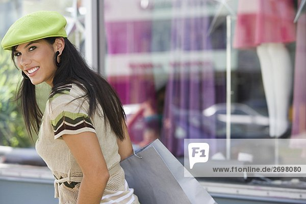 Portrait of a young woman carrying a shopping bag in front of a clothing store