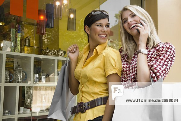 Young woman talking on a mobile phone with another young woman holding a shopping bag beside her