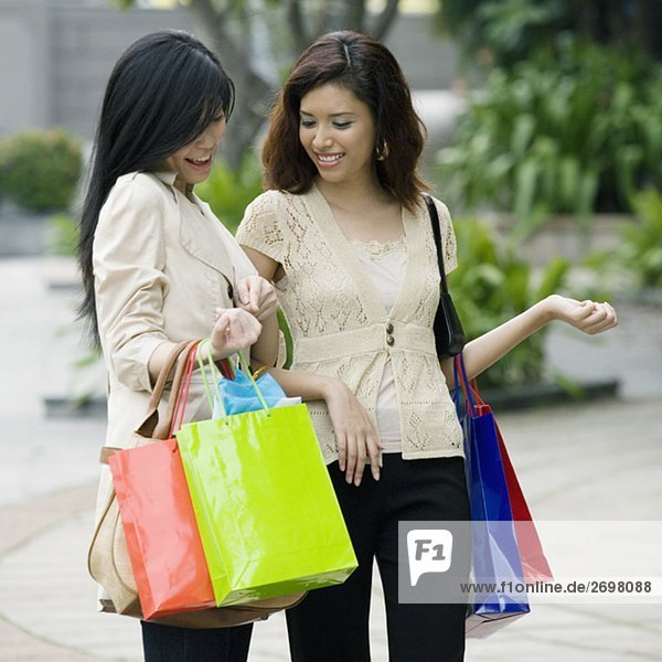 Close-up of two young women carrying shopping bags and smiling