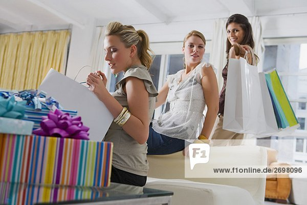 Young woman checking her shopping bags with her friends in the background