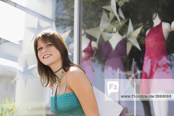 Side profile of a young woman carrying a shopping bag in front of a clothing store