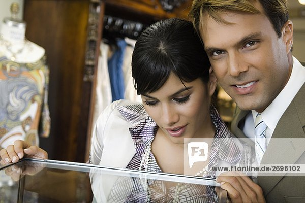 Young woman looking in a display cabinet with a mid adult man smiling beside her