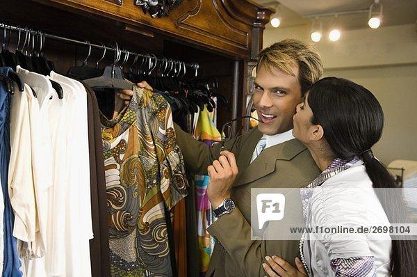 Junge Frau küssen einen Mitte Erwachsenen Mann in einem Bekleidungsgeschäft