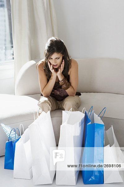 Young woman looking at shopping bags and looking worried