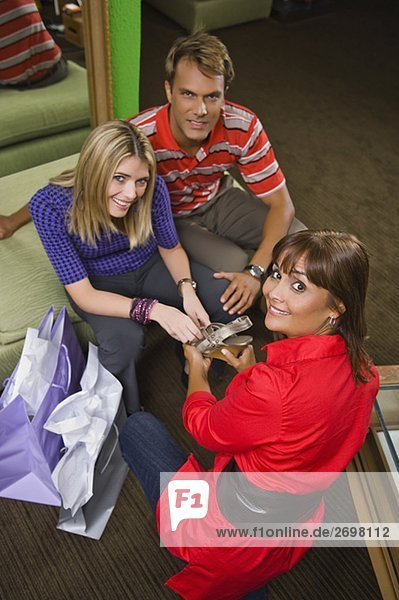 Portrait of a sales clerk showing a sandal to a young woman