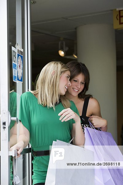 Two young women holding shopping bags and smiling