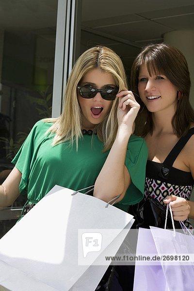 Young Woman looking überrascht mit einer anderen jungen Frau lächelnd neben ihr