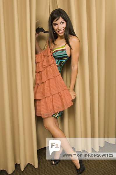 Young woman trying on a dress and smiling