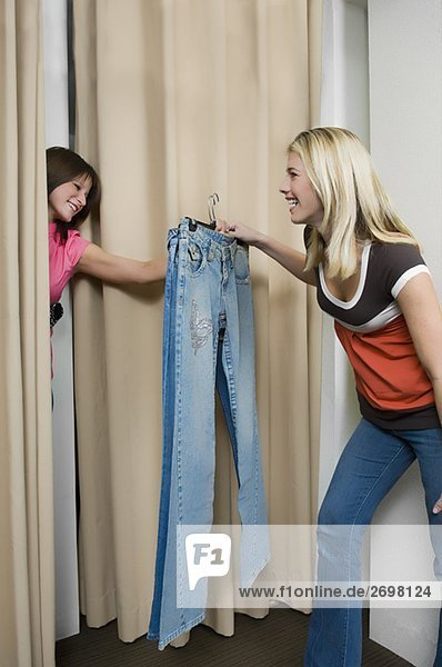 Young woman taking jeans from a sales clerk in a fitting room