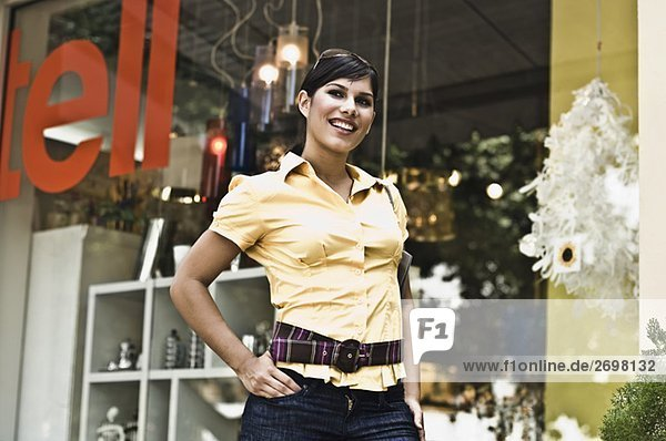 Low angle view of a young woman standing in front of a store