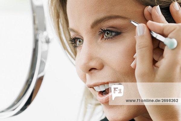 Nahaufnahme einer Mitte erwachsen Frau ihre Augenbrauen zupfen