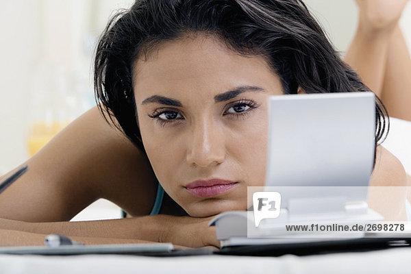 Portrait einer jungen Frau liegen auf einem Bett an ein persönlicher organizer