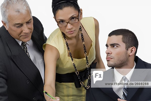 Two businessmen and a businesswoman discussing