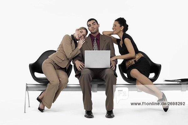 Kaufmann mit ein Laptop und zwei Geschäftsfrauen stützte sich auf seinen Schultern