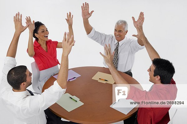 Three businessmen and a businesswoman smiling with their arms raised in a meeting