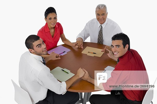 Portrait of three businessmen and a businesswoman sitting with holding their hands in a meeting