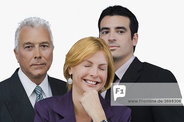 Close-up of a businesswoman smiling with two businessmen behind her
