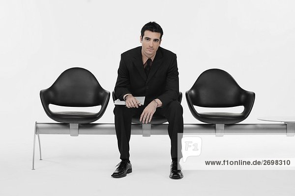 Portrait of a businessman sitting on a bench