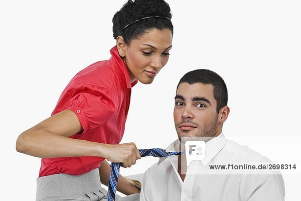 Side profile of a businesswoman pulling a businessman with his tie