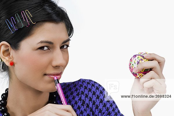 Portrait of a young woman holding rubber bands and a pen