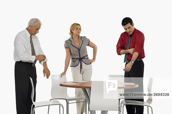 Two businessmen folding their shirt sleeves with a businesswoman standing beside them